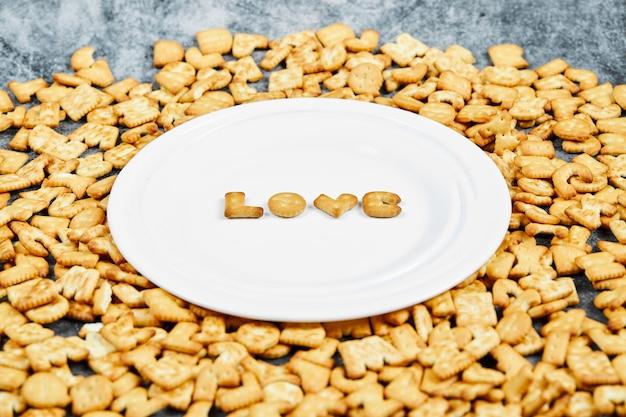 Craquelins alphabet dispersés et mot amour épelé avec des craquelins sur une plaque blanche.