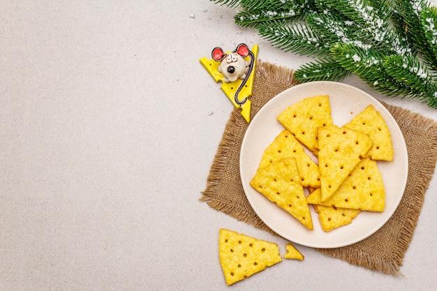 Craquelins au fromage festif, concept de collation du nouvel an. cookies, figurine de souris, branche de sapin, neige artificielle, serviette de table.