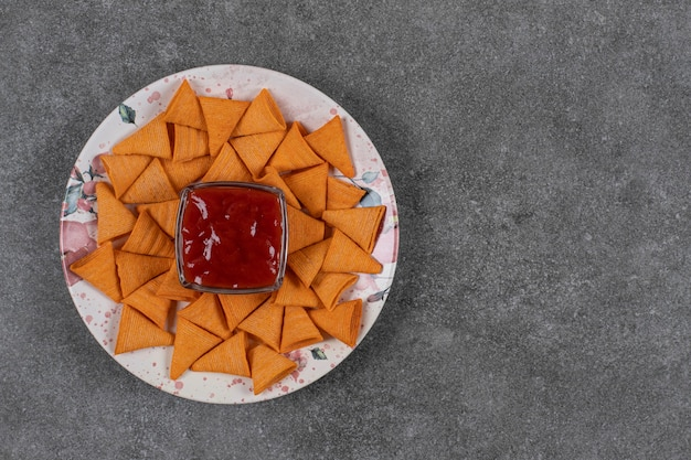 Craquelins en forme de triangle sur assiette avec du ketchup.