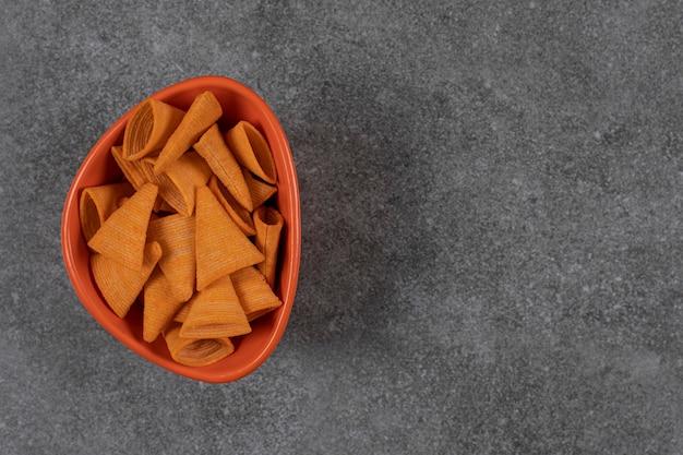 Craquelins en forme de triangle dans un bol orange.