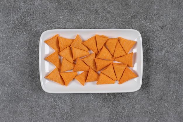 Craquelins en forme de triangle sur plaque blanche.