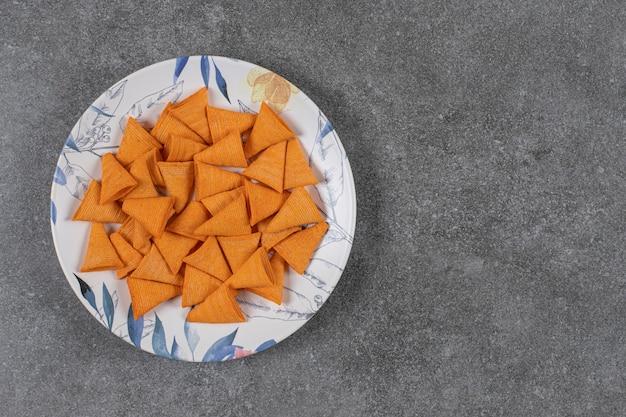 Craquelins en forme de triangle sur plaque colorée.