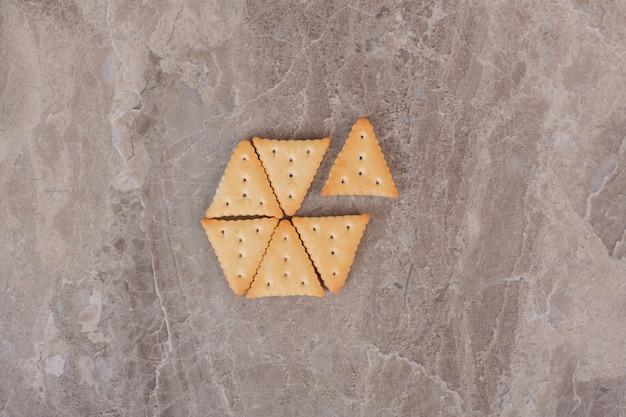 Craquelins en forme de triangle sur une surface en marbre.