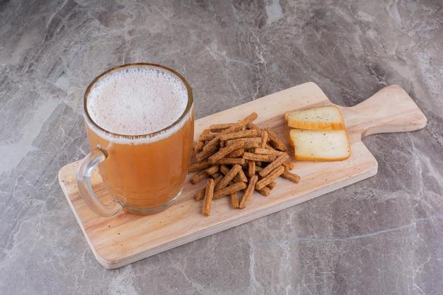 Craquelins, fromage et verre de bière sur planche de bois. photo de haute qualité