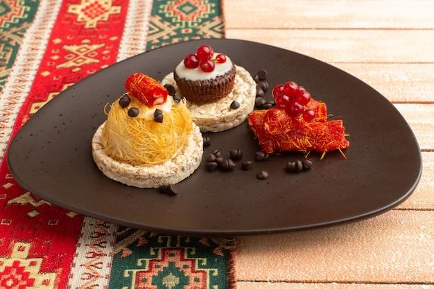 Craquelins et gâteaux à l'intérieur de la plaque brune sur crème rustique