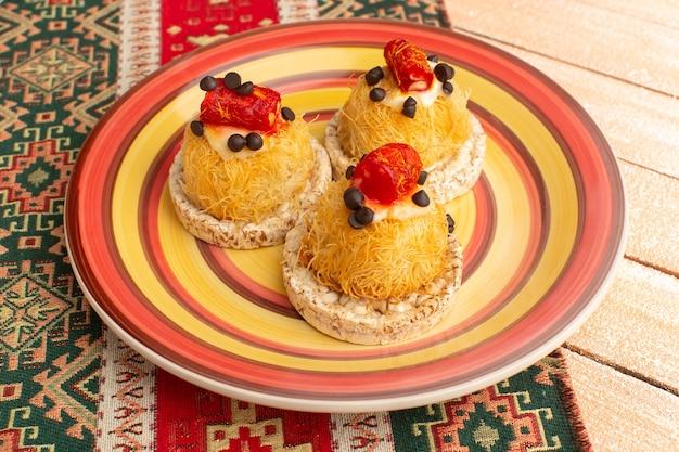Craquelins et gâteaux à l'intérieur de la plaque colorée sur rustique crème