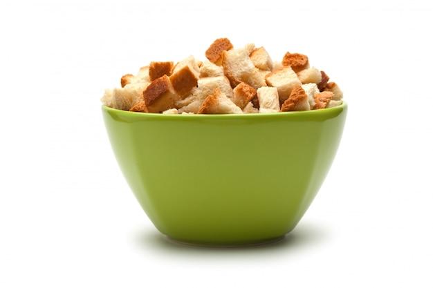 Craquelins de grains dans un bol vert isolé