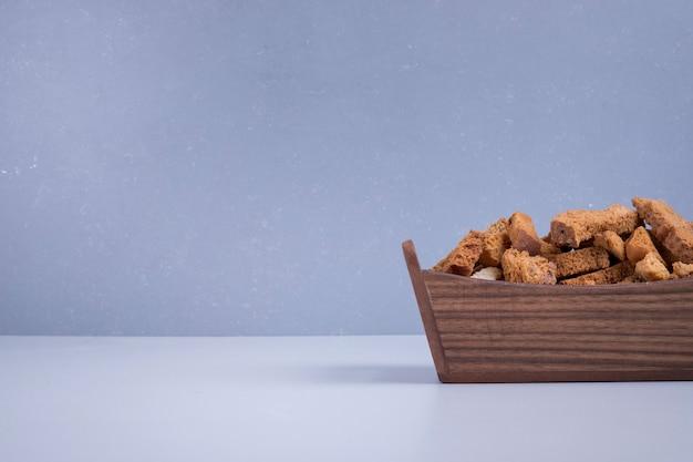 Craquelins de pain dans un plateau en bois sur bleu