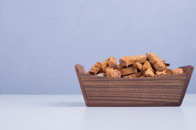 Craquelins de pain dans un plateau en bois sur fond bleu au centre