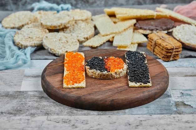 Craquelins de riz au caviar rouge et noir sur une plaque en bois. photo de haute qualité