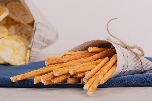 Craquelins de riz et bretzels sur nappe bleue.