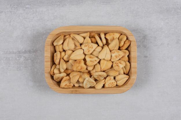 Craquelins salés en forme de coeur sur plaque de bois.