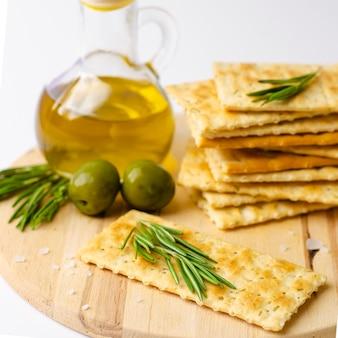 Craquelins sans gluten au romarin, olives et huile d'olive sur planche de bois.