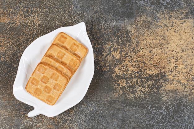 Craquelins sucrés carrés sur assiette en forme de feuille.
