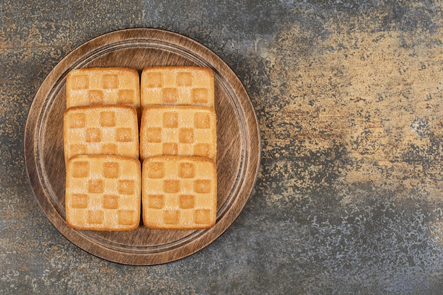 Craquelins sucrés carrés sur planche de bois.