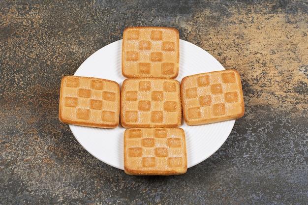 Craquelins sucrés carrés sur plaque blanche.