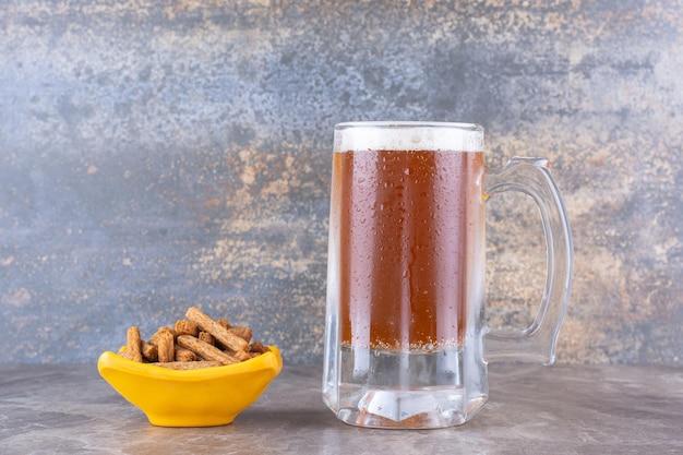 Craquelins et verre de bière froide sur table en marbre. photo de haute qualité