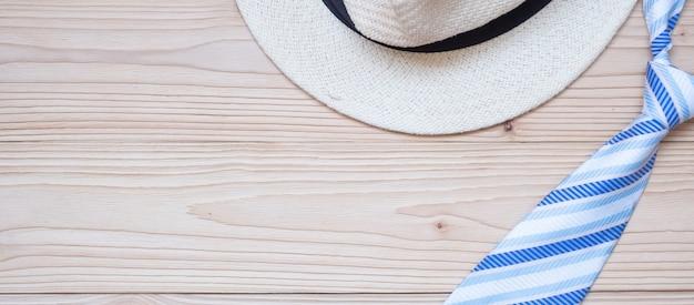 Cravate bleue et chapeau sur bois
