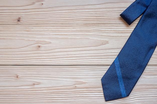 Cravate bleue sur fond en bois avec espace de copie du texte.