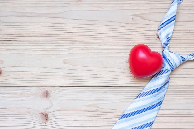 Cravate bleue et forme de coeur rouge sur bois