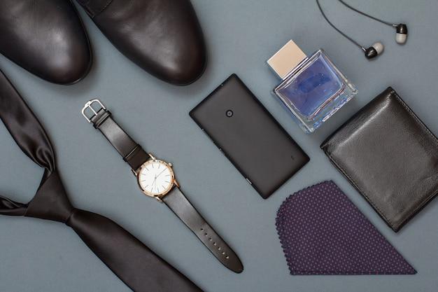 Cravate noire, chaussures pour hommes, montre avec bracelet en cuir, téléphone portable, mouchoir, sac à main en cuir, eau de cologne pour hommes et casque sur fond gris. accessoires pour hommes. vue de dessus