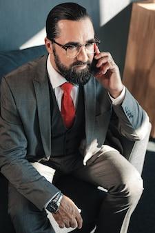 Une cravate rouge. homme d'affaires d'âge mûr élégant portant une cravate rouge appelant son partenaire pour lui rappeler la réunion