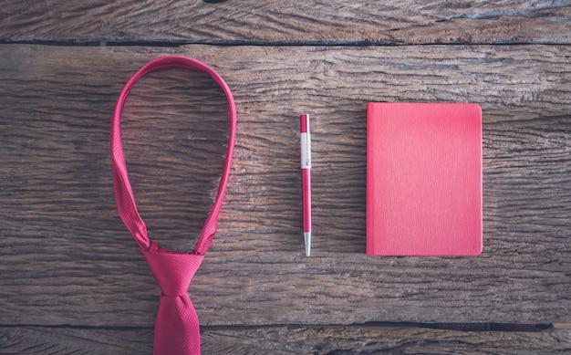 Cravate rouge, stylo, carnet de notes sur une table en bois