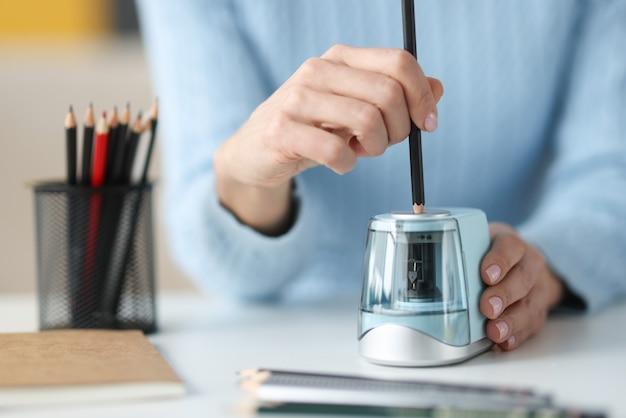 Crayon d'affûtage des mains féminines avec taille-crayon électronique gros plan