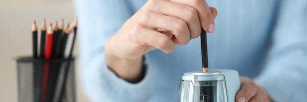 Crayon à aiguiser les mains des femmes avec le concept de papeterie agrandi de taille-crayon électronique