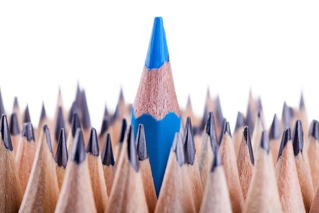 Un crayon bleu aiguisé parmi beaucoup d'autres