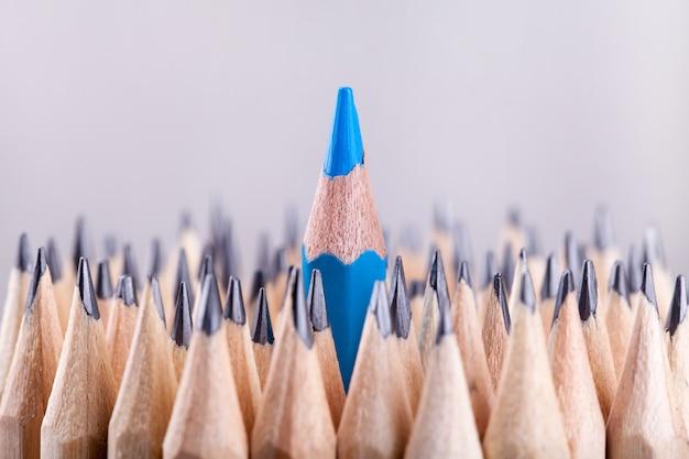 Un crayon bleu taillé parmi beaucoup d'autres