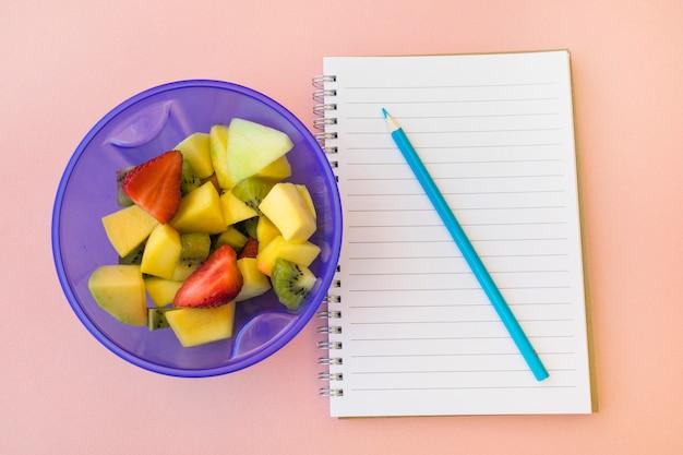 Crayon et bloc-notes près de la salade de fruits