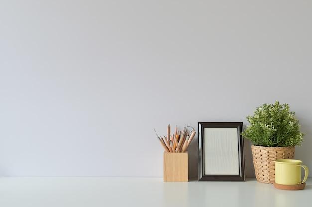 Crayon, café, cadre photo et plante sur l'espace de copie, bureau.