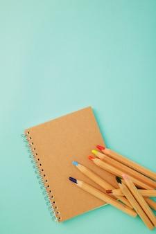 Crayon avec un cahier sur bleu