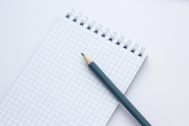 Crayon et cahier sur fond blanc, gros plan