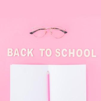 Crayon et cahier près de lunettes et d'écriture