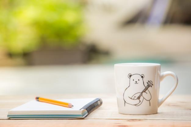 Crayon, cahier, tasse blanche sur la table en bois en plein air et copiez l'espace.