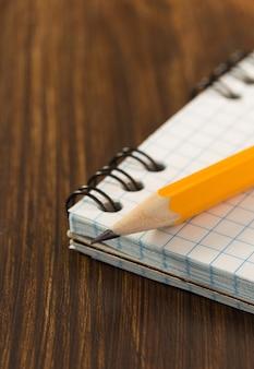 Crayon et cahier vérifié sur table en bois