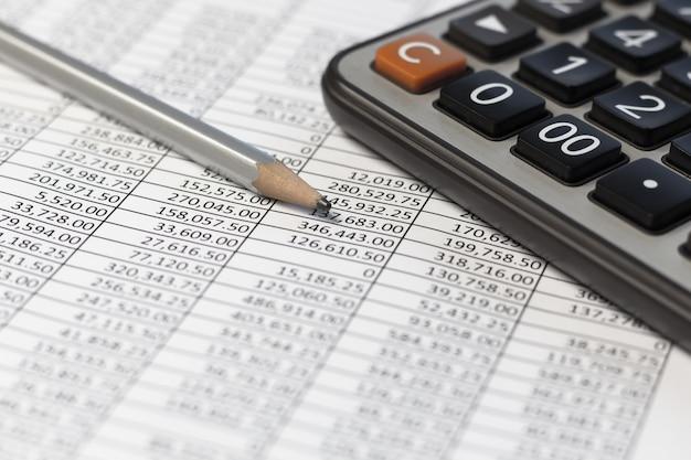 Crayon et calculatrice sur une table de bureau avec rapport de documents de compte financier.