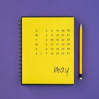 Crayon et calendrier jaune vue de dessus