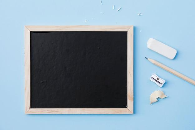 Crayon et caoutchouc près de taille-crayon et tableau noir