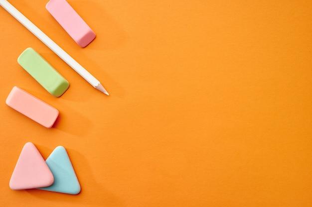 Crayon, caoutchoucs et gros plan de craie, mur orange. fournitures de bureau, accessoires scolaires ou éducatifs, outils d'écriture et de dessin