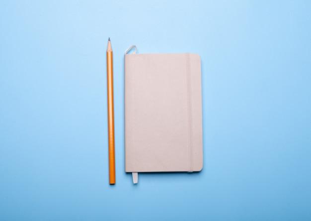 Crayon et carnet de croquis isolé sur bleu