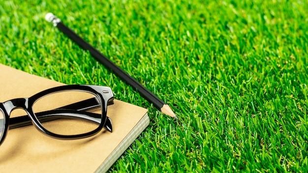 Crayon, carnet de journal et lunettes sur la pelouse verte le matin.