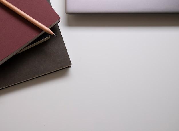 Crayon sur le carnet et ordinateur portable sur la table