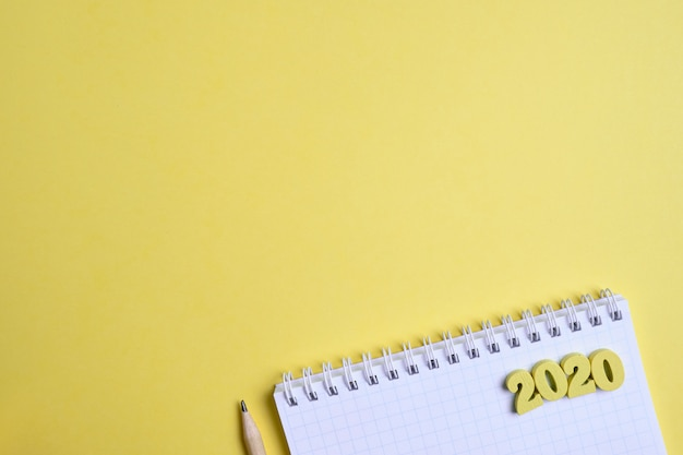 Crayon à côté d'un bloc-notes et de figures en bois 2020 sur fond jaune. le concept d'enregistrement de nouvelles tâches pour l'année. vue de dessus. copiez l'espace.