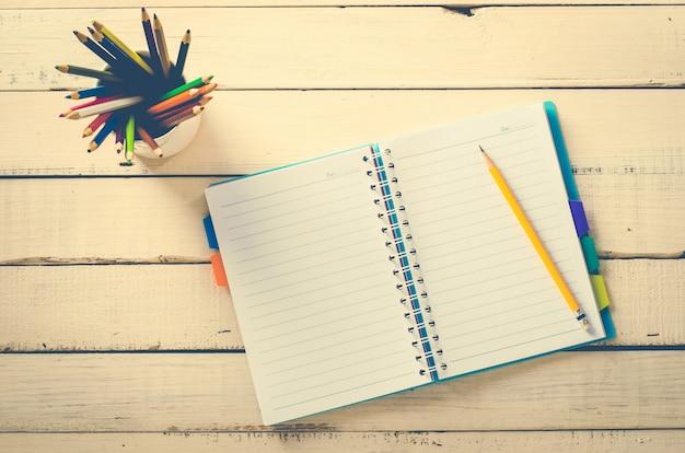 Crayon de couleur et cahier sur la table en bois rugueuse