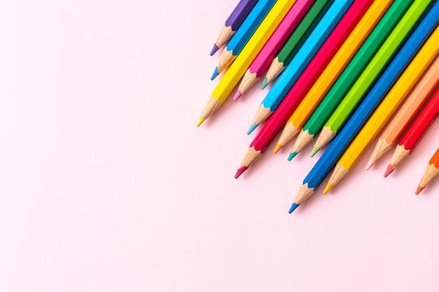 Crayon de couleur sur fond rose avec espace copie