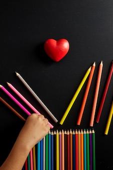 ้ crayon de couleur à la main avec forme de coeur retour à l'école bannière bannière concept