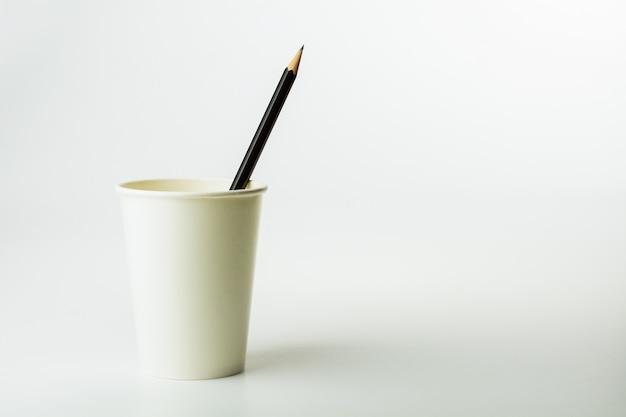 Crayon dans une tasse à café en papier sur fond blanc.